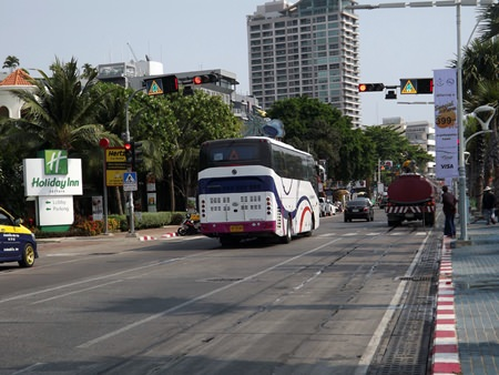This tourist bus just drives straight through the red light without stopping as tourists wait to cross the road.