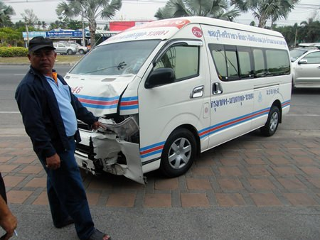 Van driver Pomuao Hadgadeang points to the damage on his van.