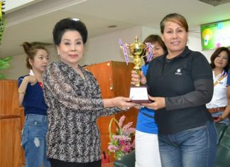 Rotary Club of Chonburi Past President Naree Jintananon (left) presents the Pattaya Mayor Itthipol Khunplome Championship trophy to Aabngern Tripong of the McDao team.