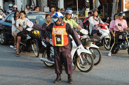 Volunteer Manit Bantherng directs traffic during peak hours in Soi Nernplabwan.