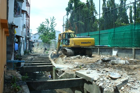 A city mandated backhoe works to expand the canal behind Soi Marine.