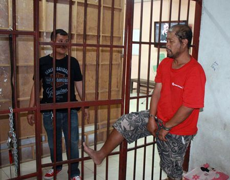 Somyos Anumat (right) shows police how he kicked open the cell door and nearly escaped.