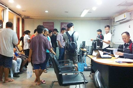 Gamblers are brought in for questioning after police raided illegal gambling dens in Pattaya and Huay Yai.