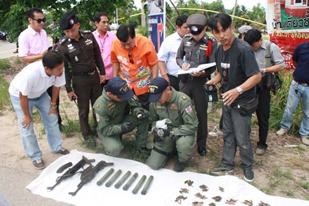 Officials inspect a cache of weapons found in Sattahip.