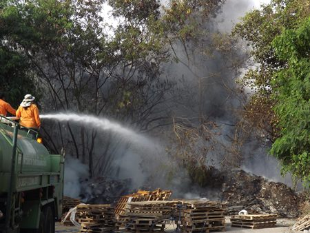 Firefighters work to bring under control a garbage fire off Thepprasit Road.