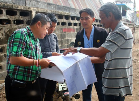 Deputy Mayor Verawat Khakhay (left) inspects the plans and the progress of flood mitigation construction in Naklua.