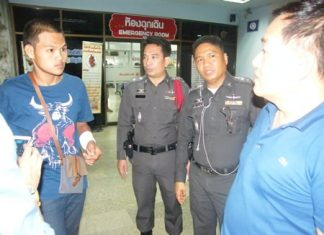Phakorn Jittham (left) talks to police after receiving a gunshot wound from allegedly unknown assailants. His friend, Buncha Wonghong, was killed in the attack.