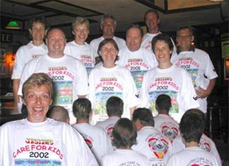 The committee models the 2002 event shirts.