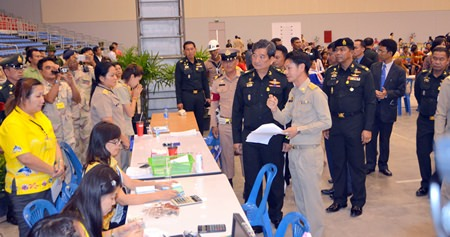Col. Sirichai Distakul (center right), armed forces chief of joint staff and chairman of the Sub-Committee on Transnational Labor and Human Trafficking, inspects the registration process for foreign workers at Huay Yai's one-stop center in the Eastern National Sports Training Center.