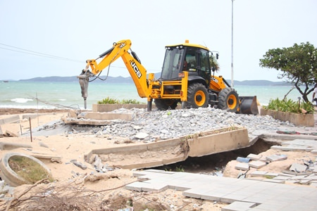 A city construction crew goes to work demolishing the damaged pavilion at Yin Yom beach.