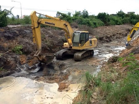 Sanitation Engineering Department workers continue to try and divert flood waters away from residential areas by digging a runoff ditch along the railroad tracks.