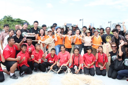 YWCA Chairwoman Praichit Jetpai (center) and YWCA members join members of the Naklua Bay Group, students, and local fishermen to make artificial grass from ropes to create seabeds to return balance to the aquatic environment.