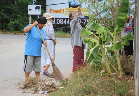 Krung Thai Village residents clean along the road in their community to pay homage to Her Majesty Queen Sirikit.
