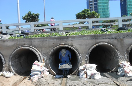 Sanitation Engineering Department staffers clean out sand and debris from flood water drainage pipes at Bali Hai Pier, part of the city's ongoing effort to mitigate flooding when the heaviest rains hit in September and November.