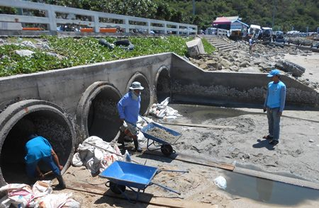 Sanitation Engineering Department crews clear sand, garbage and natural debris from the tail ends of the pipelines carrying flood water from eastern parts of the city.