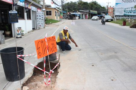 "Community leader Chaimongkhol Bunsuud points out how the road is still damaged.  The sign reads, ""the road is collapsing""."