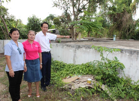Vutikorn Kamolchote, President of Rotary Club of Jomtien-Pattaya, points towards the center's water tank.
