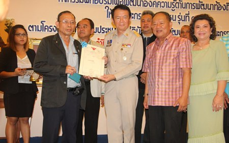 Likit Thailaemthong receives a certificate of appreciation from Banglamung District Chief Sakchai Taengho and Nongprue Mayor Mai Chaiyanit for donating land to Nongprue Municipality.