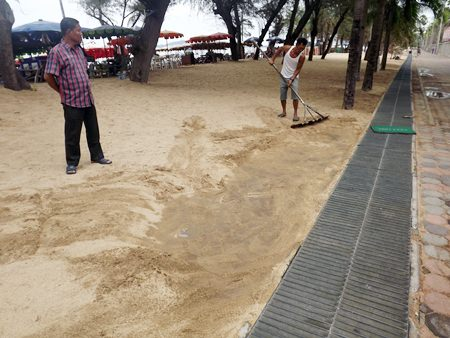 Beach vendors brush sand off the footpath to prove that it was all buried.