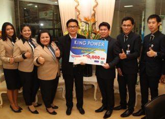 King Power Pattaya Operations Manager Sumitr Wongsamart (center right) presents 10,000 baht to buy 60 sporting outfits for students of Pattaya's schools to Deputy Mayor Wutisak Rermkitkarn (center left).