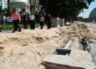 Officials inspect the area of Wong Amat Beach where heavy rain interrupted construction of new waste water pipes, causing sewage to empty into the sea.