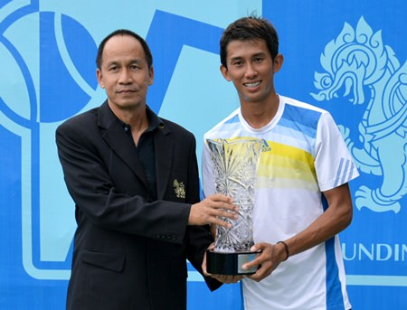 Singha representative Sruang Jantrautai (left) presents the crystal cut trophy to men's champion Phassawit Burapharitta.