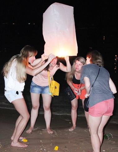 Foreign teenage girls float lanterns together.