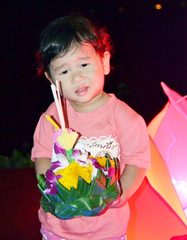A boy poses before floating his krathong.