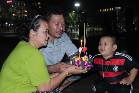 A family makes a wish before floating their krathong into the sea at Pattaya Beach Soi 4.