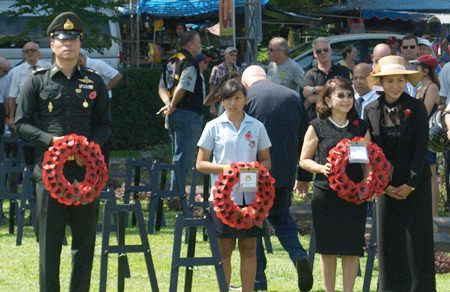 A GIS student carries a wreath at a service in Kanchanaburi.