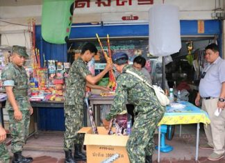 District Chief Phawat Lertmukda (right) leads a team of volunteers, police and navy personnel through the Sattahip Market raiding vendors selling firecrackers and khom loys.