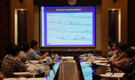 Officials look over a plan for new, wider drainage pipes, for which, evidently, Pattaya coffers don't have the funds.