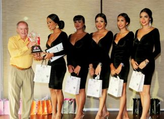 Event organizer Tony Sales (left) presents the winning trophy to the Sensations Bar Team.