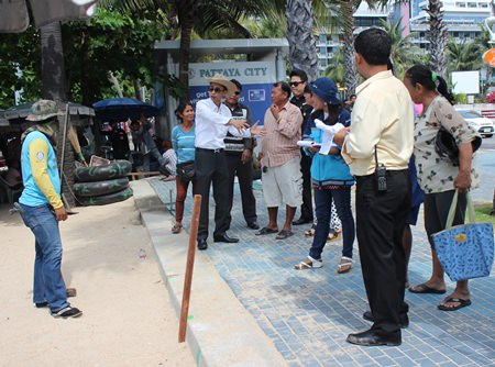 Pattaya Permanent Secretary Pakorn Sukhonthachat instructs city workers on where to drive their stakes as Pattaya and military officials begin outlining new zones for beach chairs and umbrellas on Pattaya Beach. The new regulations call for 10 meters of empty sand every 100 meters. Inside each zone, vendor concessions are to be separated by one meter.