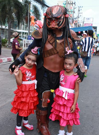 """Children pose with a character from the movie """"Predator""""."""