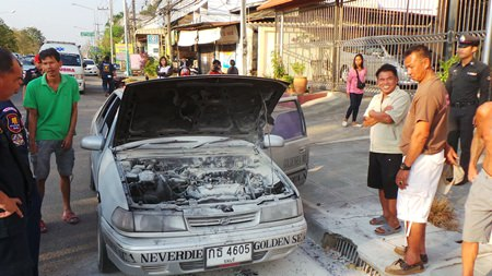 Singhnart Wattanasri (front, right) looks over his burnt out car as others try to console him.