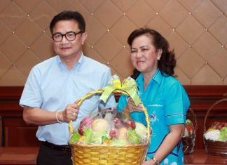 Pattaya Women's Development Group President Nawarat Khakhay presents a New Year gift basket to Deputy Mayor Wutisak Rermkitkarn to thank him for attending the group's meeting.