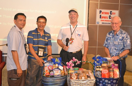 Pattaya Mail reporters Surasak Huasoon and Urasin Khantaraphan show the 3 gift baskets donated by Urasin to PCEC Chairman Roy Albiston and Vice Chairman Richard Smith, which will be raffled off by the PCEC for funds to donate to charity.