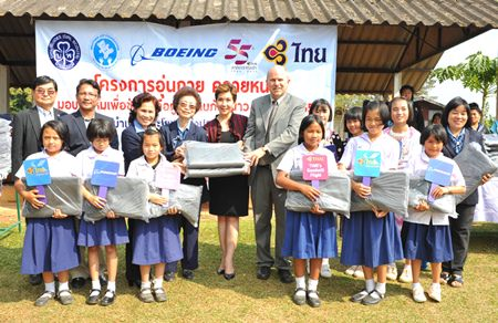 Petchpring Sarasin (back row, fifth from left), THAI Vice President of Corporate Image & Communications Department, with David Bizar (back row, sixth left), Field Service Regional Manager of the Boeing Company (Thailand), hand over 1,000 blankets that were donated to students in Wieng Pa-Pao district, Chiang Rai province, which were received by Chao Dararat Na Lampoon (back row, fourth left), alongside Prasert Jitpleecheep (back row, second left), Marshal of Wieng Pa-Pao district, Chiang Rai province.