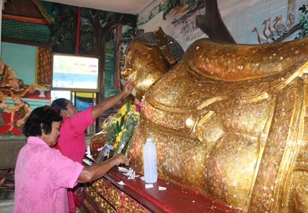 People place gold leaf on the reclining Buddha image at Suthawas temple in Nongprue.