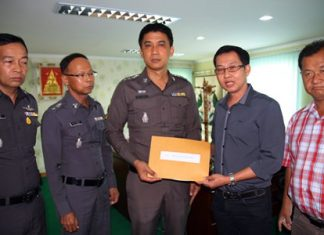 Kantapon Sukumalin hands his complaint over to Pattaya police superintendent Pol. Col. Sukthat Pumpunmuang.