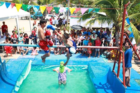 Youngsters battle in the traditional sea boxing competition - stay on the pole and you win, fall off and you lose.