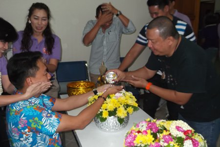 Officials and staff poor scented water into the palms of Superintendent Pol. Col. Prapansak Prasarnsuk.