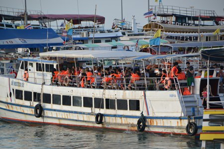 Koh Larn ferry operators are being criticized for allegedly overcharging passengers, violating fare rules for children, and causing confusion by not putting vessel numbers on tickets, causing some passengers to board the wrong boat. Boat operators tried to defend their positions, but Deputy Mayor Ronakit Ekasingh insisted they follow the law. (Photo by Urasin Khantaraphan)