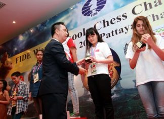 Neoh Kean Boon (centre), resident manager of Dusit Thani Pattaya, hands trophies to the winners of the Under-15 and 17 age categories for girls during the awards ceremony for the World Schools Individual Chess Championships 2015, Thursday, May 14.
