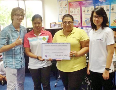 St. Andrews CAS students deliver a 100,000thb check to Operation Smile directors.