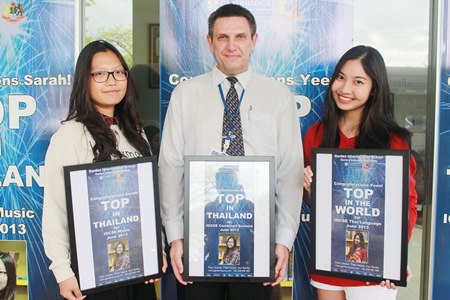 GIS Principal Dr Stuart Tasker presents Sarah (left) and Yeen (right) with their posters. Sarah is going to study at UCLA, whilst Yeen will be going to study at Durham University.