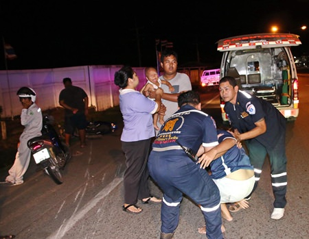 The child is crying, but relatively unhurt as rescue workers help the mother into a waiting ambulance.