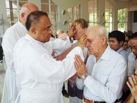 Fr. Corsie Legaspi lays his hands on the forehead of those who seek help.