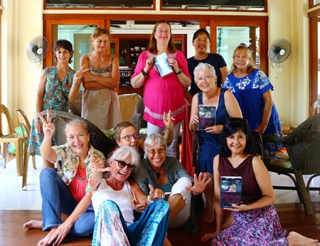 """Pattaya Book Group members pose with copies of Daniel M Dorothy's """"Mango Rains' at their monthly meeting on September 29."""